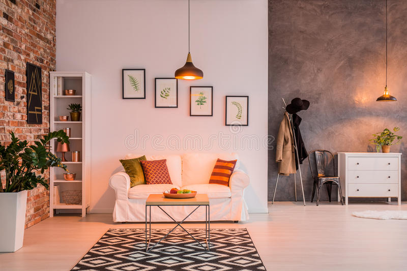 Spacious livign room with couch. Spacious living room with brick wall, couch, table and lamp royalty free stock photo