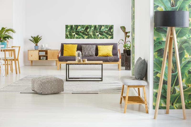 Spacious living room interior. Wooden lamp and patterned pouf in green and yellow spacious living room interior with bench royalty free stock photography
