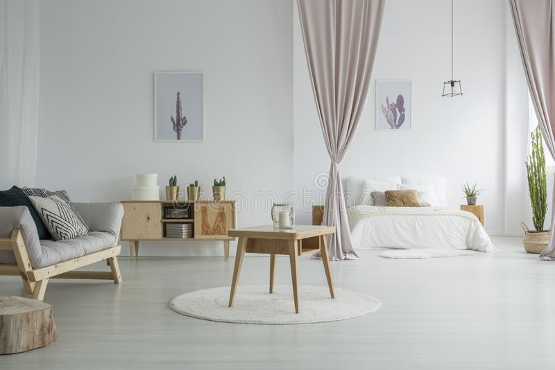 Spacious living room with bedroom. Spacious living room with wooden table on white carpet, rustic cupboard and grey sofa near open bedroom royalty free stock images