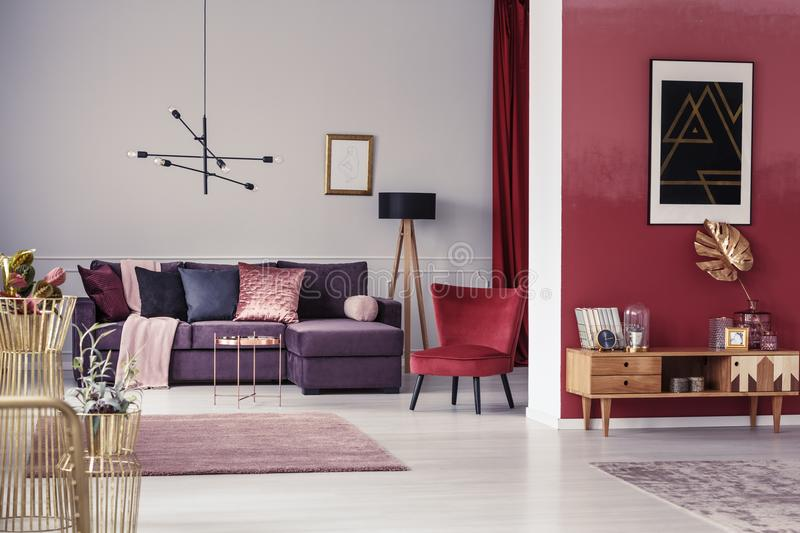 Spacious apartment. Spacious, maroon apartment interior with corner sofa, red armchair and wooden cupboard stock photos