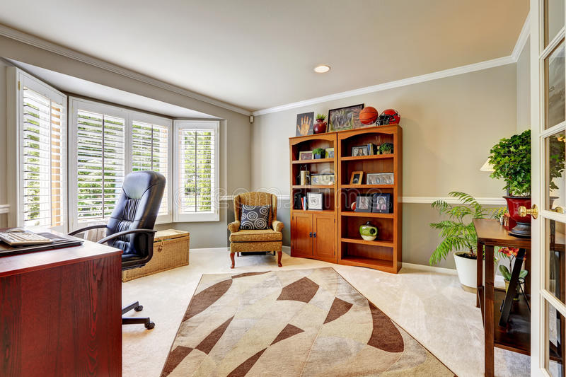 Spacious office room interior with flowers. Spacious office room with cabinet, antique armchair, desk stock photos