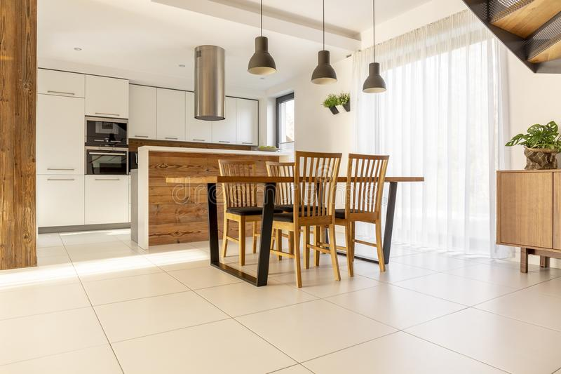 Spacious, open kitchen and dining room with wooden table and chairs, large window, white cupboards and tiles on the floor. Real p royalty free stock photo