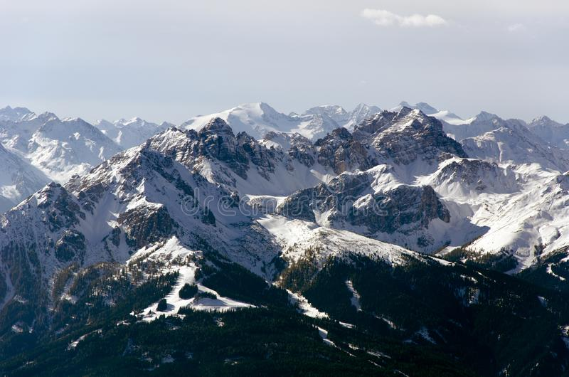 A spacious panoramic view of the Alps mountains partially covered with the snow stock photo