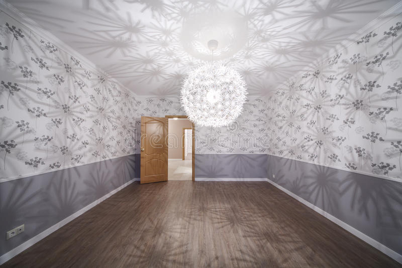 Spacious room with unusual chandelier and opened door royalty free stock photos