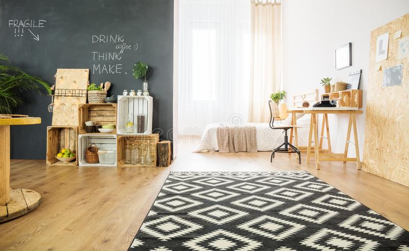 Spacious studio with bed and crates. Spacious studio apartment with double bed, crates against blackboard wall, carpet and desk stock photo