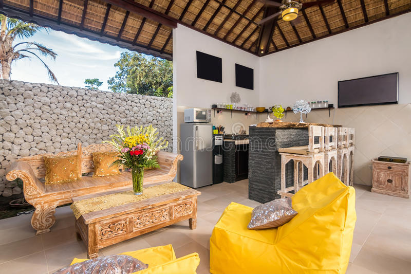 Spacious Villa Interior and living room. Beautiful living room villa interior in Bali property, outdoor style, wooden chair and sofa royalty free stock image
