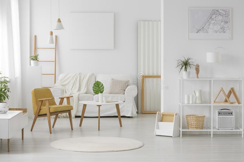 Spacious, white living room interior. With sofa, ladder, chair, table, shelves, posters, rug and wooden elements royalty free stock photos