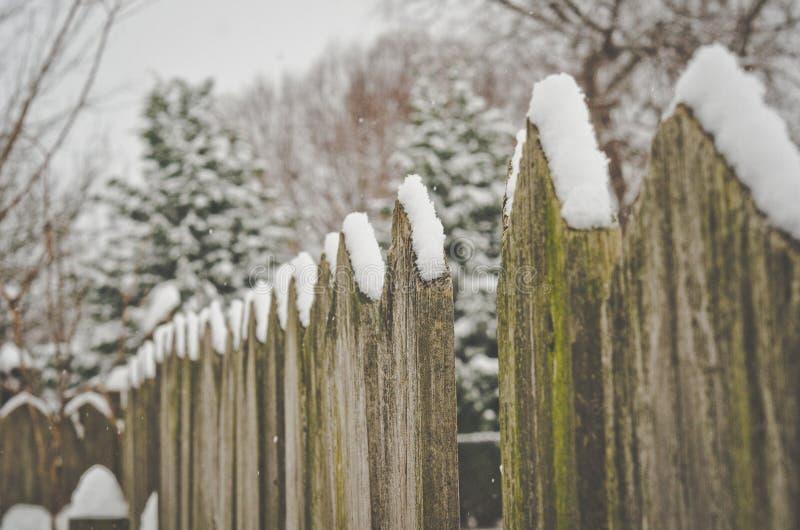 Spadać śnieg na nieociosanym ogrodzeniu obrazy stock