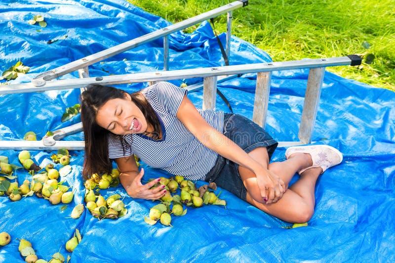 Spadać młodej kobiety lying on the beach raniący na zmielonej pobliskiej drabinie zdjęcia royalty free