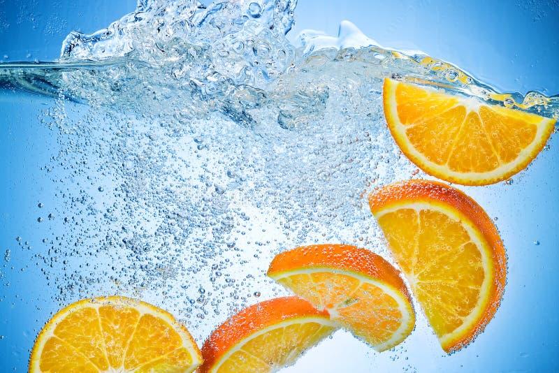 spadać pomarańczowi plasterki bryzgają pod wodą obrazy royalty free
