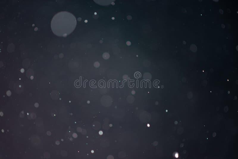 Spada śniegu lub deszczu bokeh tekstura na czarnym zmroku - błękitny tło zdjęcie stock