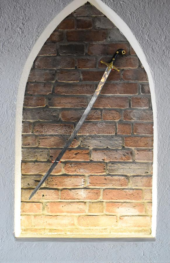Spada d'acciaio medievale contro i precedenti del muro di mattoni Spada brillante antica utilizzata come decorazione fotografia stock