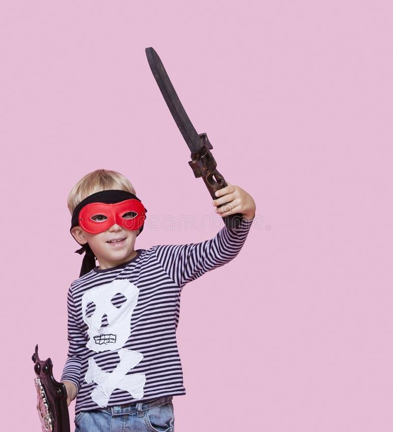 Spada e schermo d'uso della tenuta della maschera di occhio del giovane ragazzo felice sopra fondo rosa immagine stock libera da diritti