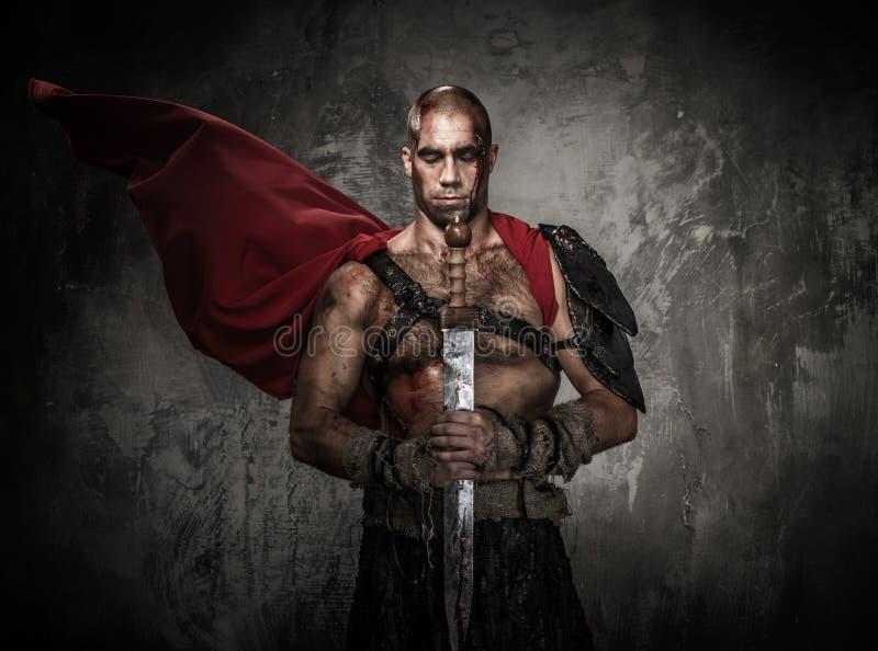 Spada ferita della tenuta del gladiatore fotografia stock