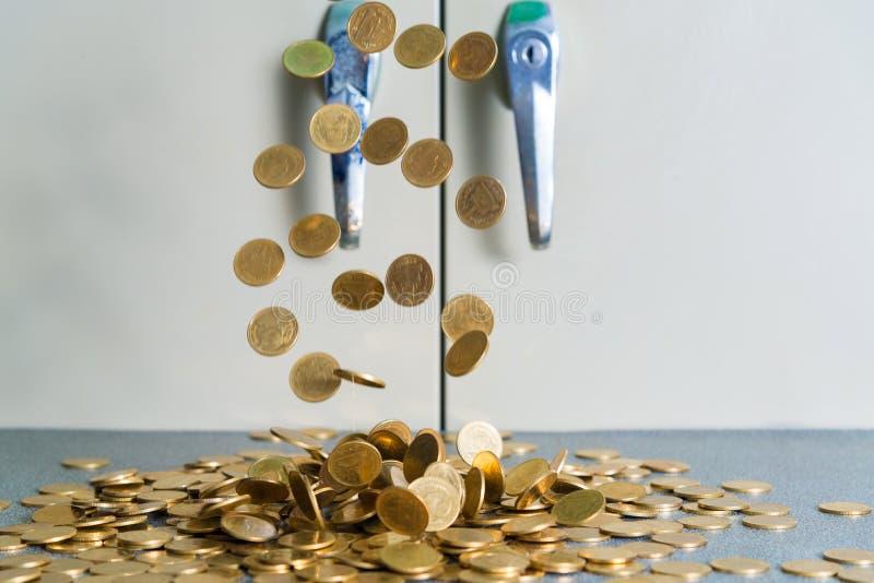 Spada złocistych monet pieniądze na biuro stole z dokumentu gabineta b fotografia stock