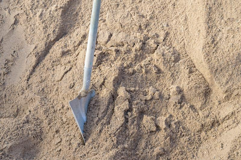 A spade stands in a pile of sand royalty free stock photography