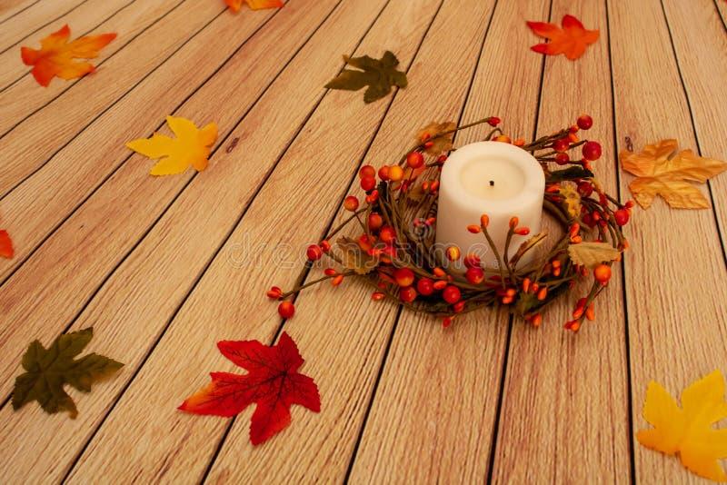 Spadku wystroju Biała świeczka z świeczka pierścionkiem, liście na Muślinowym tle obraz stock
