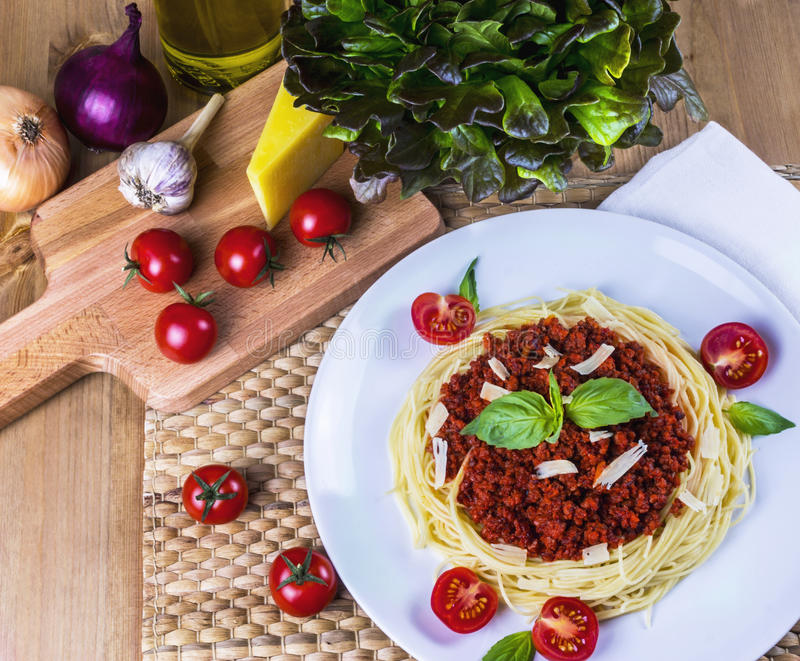 Spagetti bolognese. With vegetables on wooden table stock images