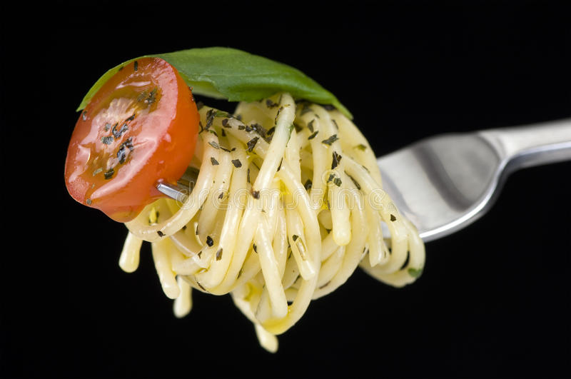 Spagetti on Fork. Spagetti with tomato and basil on fork, black background stock image