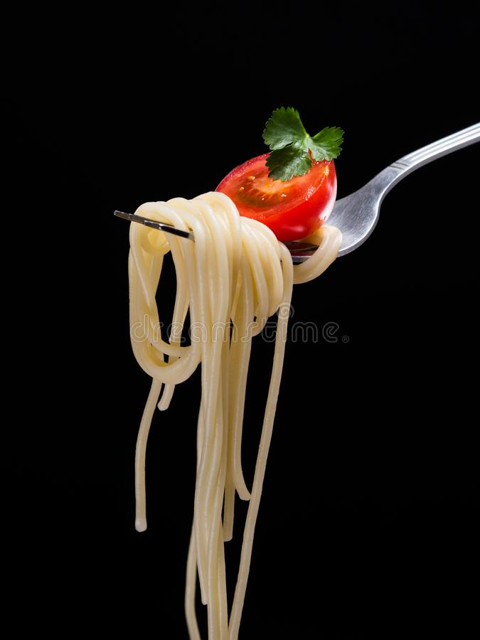 Delicious spagetti on fork. Spagetti on the fork with tomato and parsley on the black background.Vertical stock photo