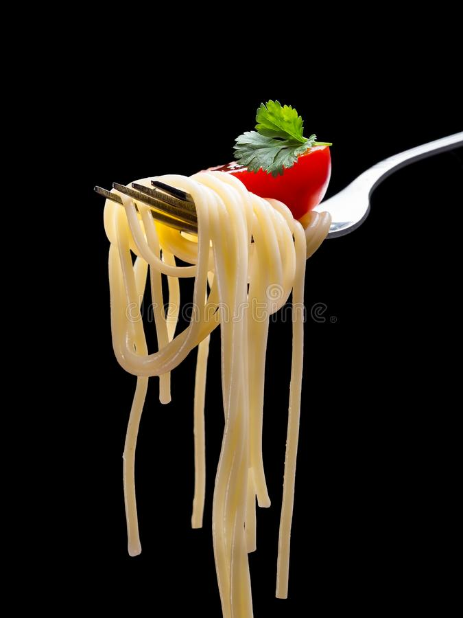 Spagetti on fork. Spagetti on the fork with tomato and parsley on the black background.Vertical stock photography