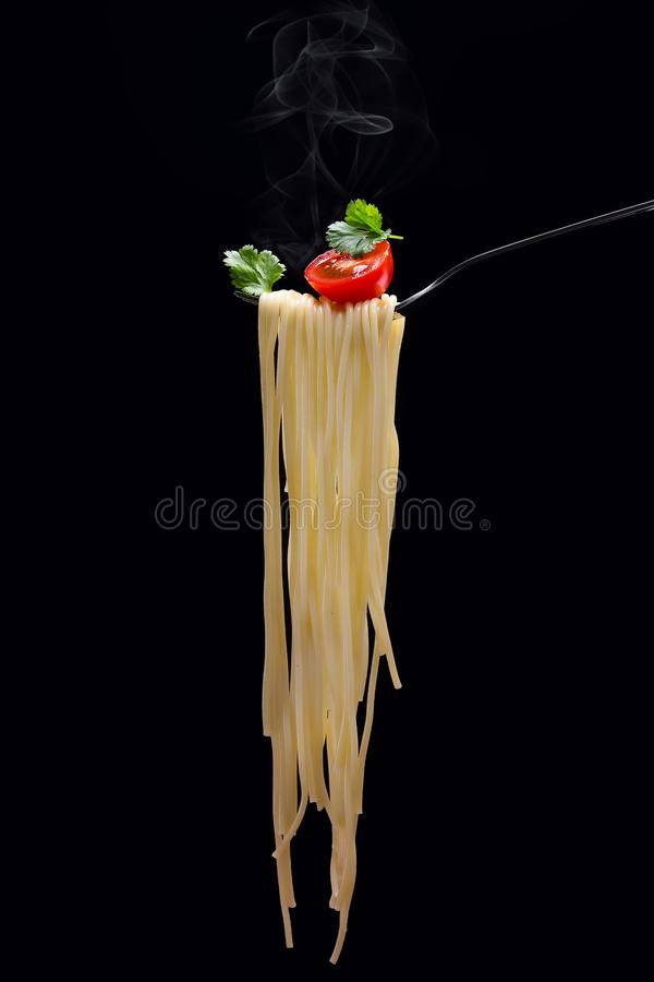 Spagetti on fork. Vertical. Hot spagetti on the fork with tomato and parsley on the black background.Vertical stock photos