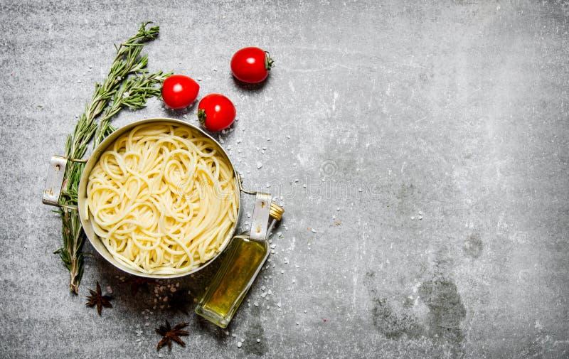 Spagetti i pannan med tomater, olivolja och örter royaltyfria foton