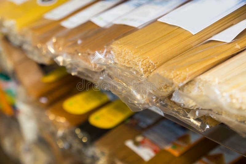Spagetti i plast- f?rpacka p? hyllor royaltyfri bild