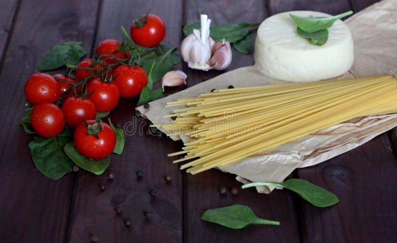 Spagetti körsbärsröda tomater, ost, vitlök, spenat, peppar på mörk wood bakgrund fotografering för bildbyråer