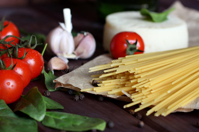 Spagetti körsbärsröda tomater, ost, vitlök, spenat, peppar på mörk wood bakgrund royaltyfri foto