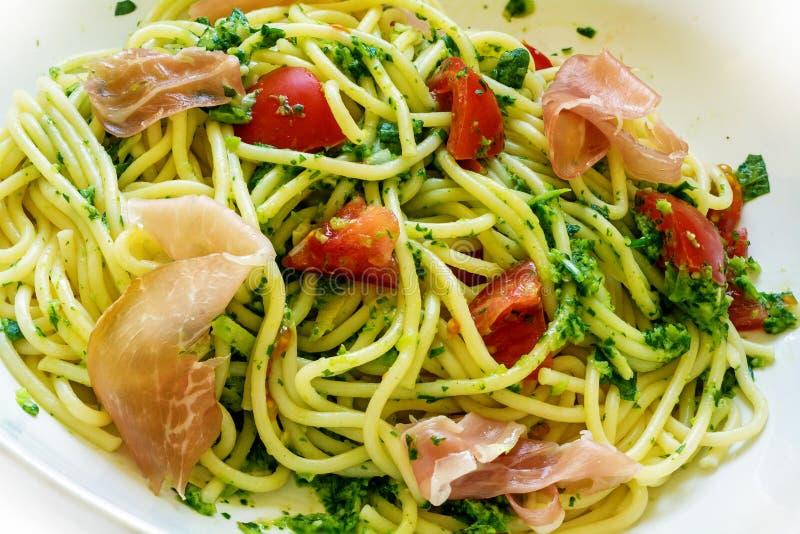 Spagetti med grön pesto, prosciuttoen och tomater royaltyfria foton
