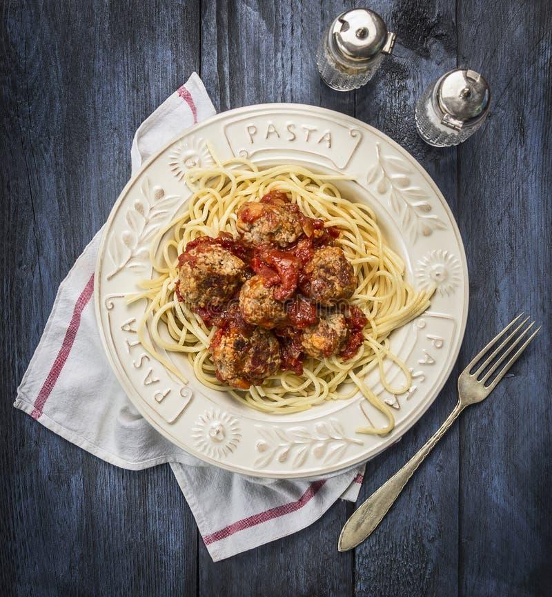 Spagetti med läckra köttbullar som göras från jordnötkött i en kryddig tomatsås med salt peppar och gaffel i en platta med inscri royaltyfri bild