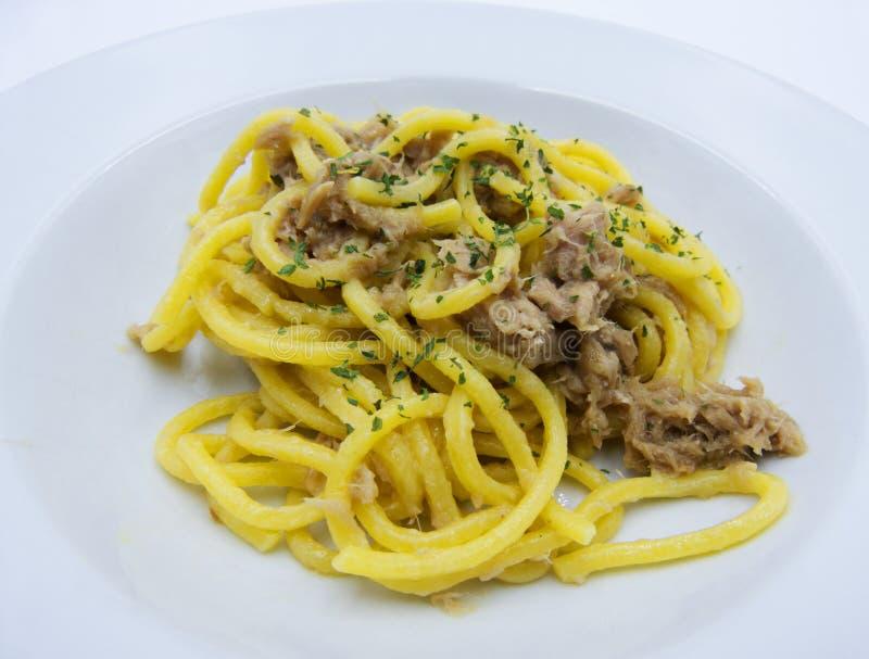 Spagetti med tonfisk på vit bakgrund, italiensk mat arkivfoto