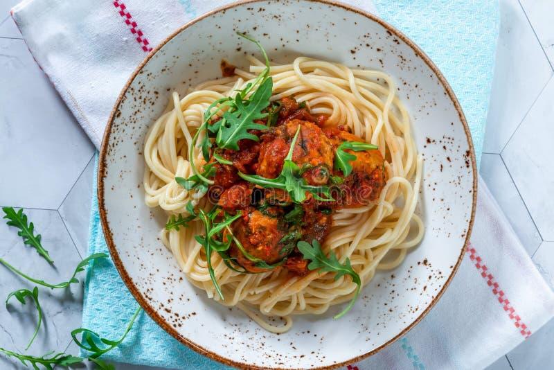 Spagetti med tonfiskbollar i kryddig tomatsås royaltyfri bild