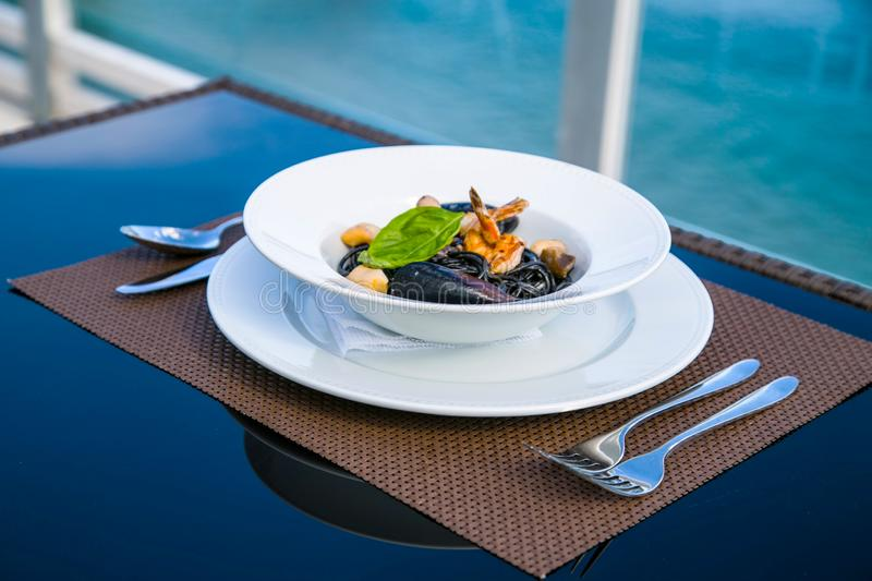 Spagetti with seafood on a plate. Delicious black cuttlefish ink spagetti with grilled shrimps, mussels, basil and mashrooms, served on white plate. Close up stock image
