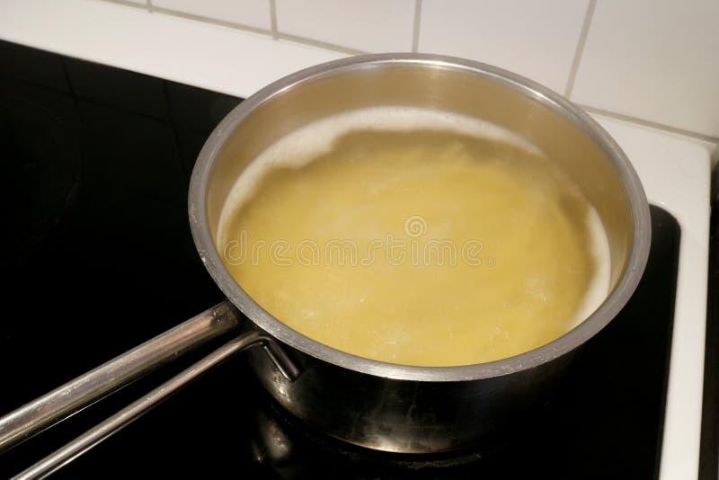 Spagetti som kokar i en rostfritt stålkastrull på en kökugn arkivbild