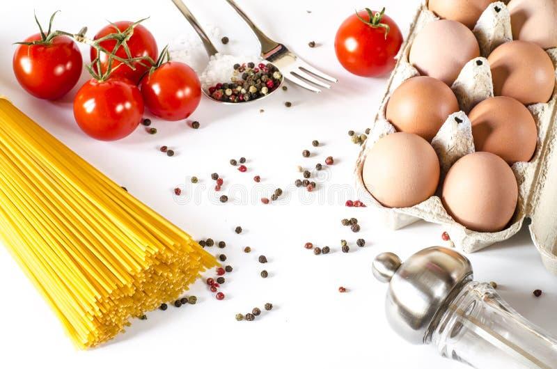 Spagettil?gn p? en vit bakgrund, tillsammans med k?rsb?rsr?da tomater, en sked och en gaffel royaltyfria bilder