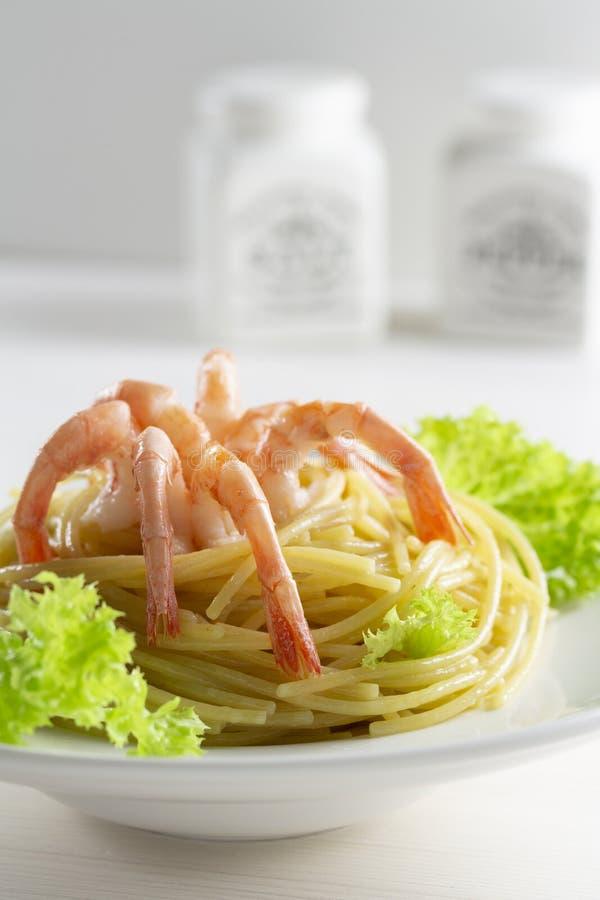 Spagettipasta med kräftaräkaräkor, olivolja och sidor för grön sallad Pasta med skaldjur, räkasvansar i form av a arkivfoton