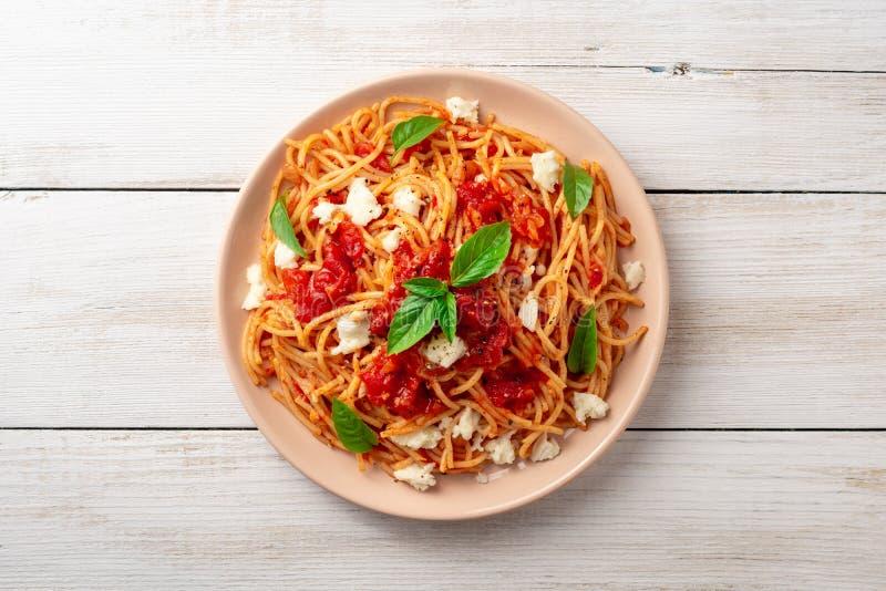 Spagettipasta med tomatsås, mozzarellaost och ny basilika i platta på vit träbakgrund royaltyfri bild