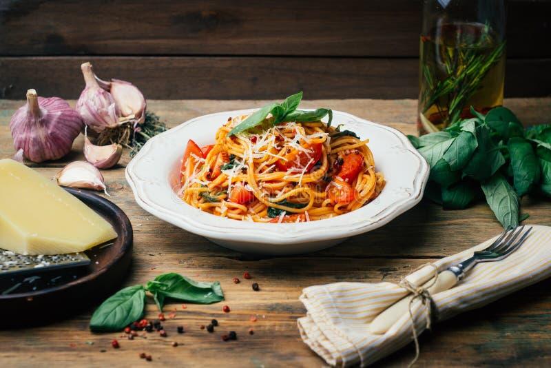 Spagettipasta med tomatsås, parmesan och basilika på en vit platta Den klassiska tomatspagettin: vegetarisk tomatbasilika royaltyfria bilder