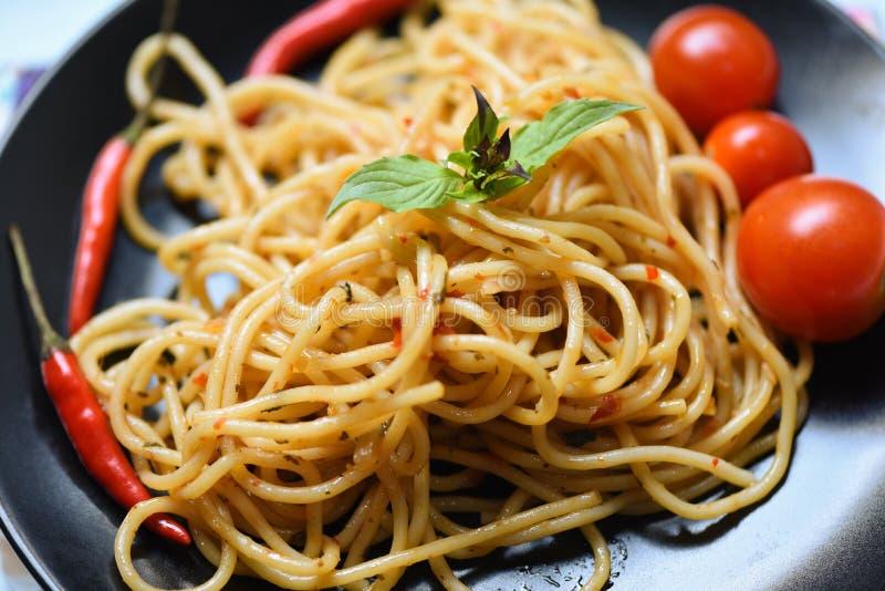 Spagettipasta och tomatchili och basilika lämnar grönsaker - traditionell läcker italiensk matspagetti som är bolognese på platta royaltyfri bild