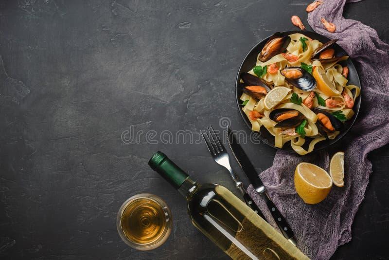 Spagettivongole, italiensk havs- pasta med musslor och musslor, i platta med örter och exponeringsglas av vitt vin på den lantlig royaltyfria foton