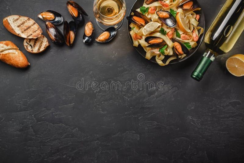 Spagettivongole, italiensk havs- pasta med musslor och musslor, i platta med örter och flaskan av vitt vin på den lantliga stenen arkivfoton