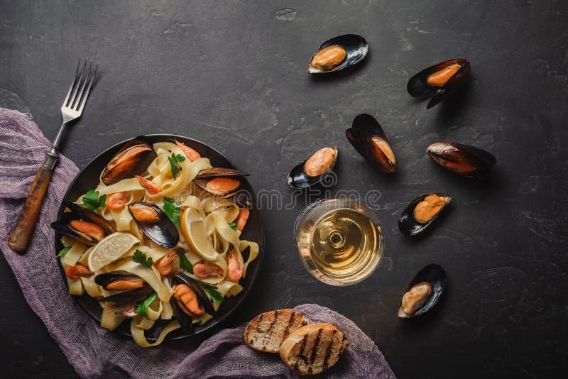 Spagettivongole, italiensk havs- pasta med musslor och musslor, i platta med ?rter och exponeringsglas av vitt vin p? den lantlig royaltyfria foton