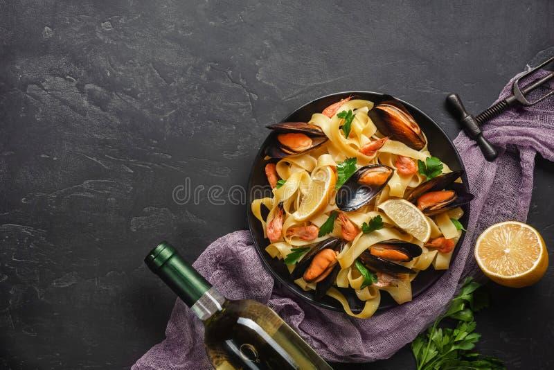 Spagettivongole, italiensk havs- pasta med musslor och musslor, i platta med ?rter och exponeringsglas av vitt vin p? den lantlig royaltyfri fotografi