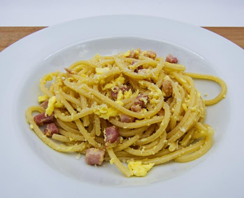 Spaghetti alla carbonara w białym naczyniu, włoski makaron na drewnianym stole, zdjęcie stock