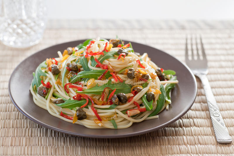 Spaghetti with arugula, chili and onions royalty free stock photo