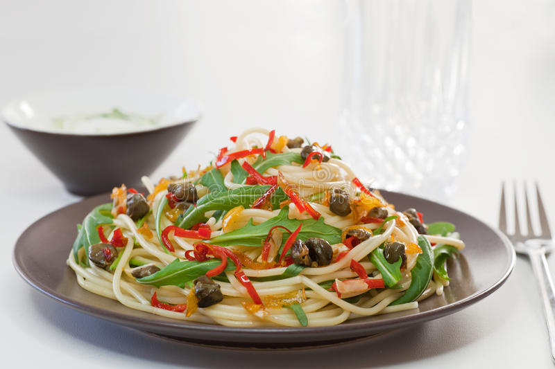 Spaghetti with arugula, chili and onions stock photos