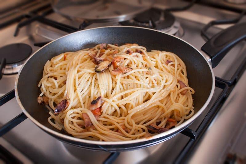 Spaghetti avec des palourdes dans la poêle sur des poêles photographie stock