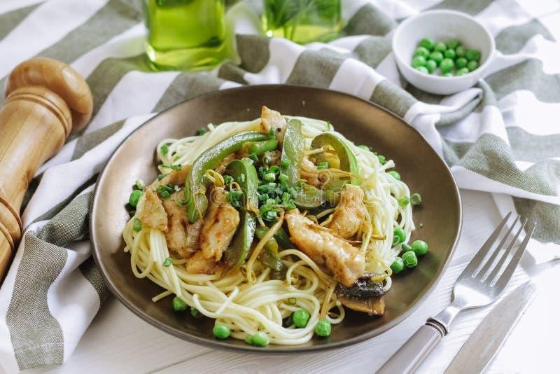 Spaghetti avec du blanc de poulet grillé et paprika vert, pois et oignon vert images stock